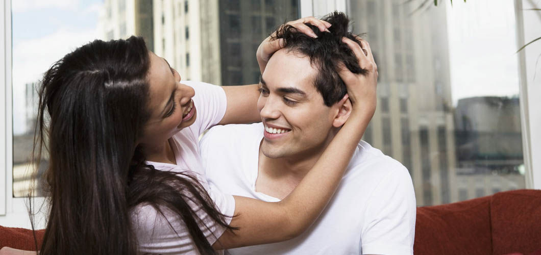 Young Woman Rubbing her Boyfriend's Head
